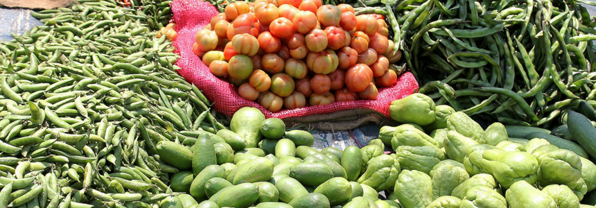 A range of chillies, tomatoes and vegetables at a market.